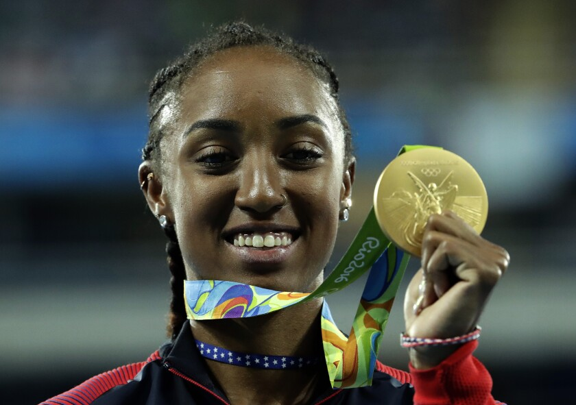 """FILE - In this Thursday, Aug. 18, 2016 file photo, Gold medal winner Brianna Rollins from the United States shows off her medal during the medal ceremony for the women's 100-meter hurdles final during the athletics competitions of the 2016 Summer Olympics at the Olympic stadium in Rio de Janeiro, Brazil. Brianna Rollins-McNeal has been banned for five years in a doping case it was reported on Friday, June 4, 2021. The decision rules her out of this year's Tokyo Games and the 2024 Paris Games. The Athletics Integrity Unit says the American's second career ban was for """"tampering within the results management process"""" of doping control samples. The 29-year-old hurdler's ban runs to August 2024. AP Photo/Dmitri Lovetsky, File)"""