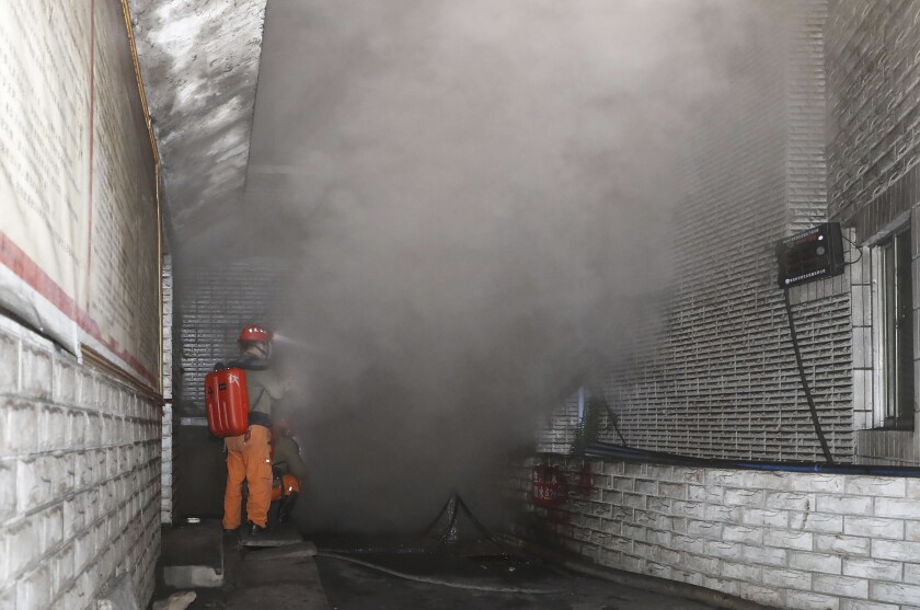 In this photo released by Xinhua News Agency, rescue workers gauge the density of carbon monoxide in the smog at the entrance of the coal mine in Yongchuan District of Chongqing, southwestern China, Friday, Dec. 4, 2020. China's state TV says more than a dozen coal miners have been killed by high levels of carbon monoxide in the country's southwest. (Huang Wei/Xinhua via AP)
