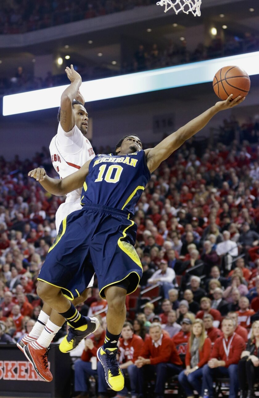 Michigan's Derrick Walton Jr. (10) goes for a layup against Nebraska's Ray Gallegos (15) in the first half of an NCAA college basketball game in Lincoln, Neb., Thursday, Jan. 9, 2014. (AP Photo/Nati Harnik)