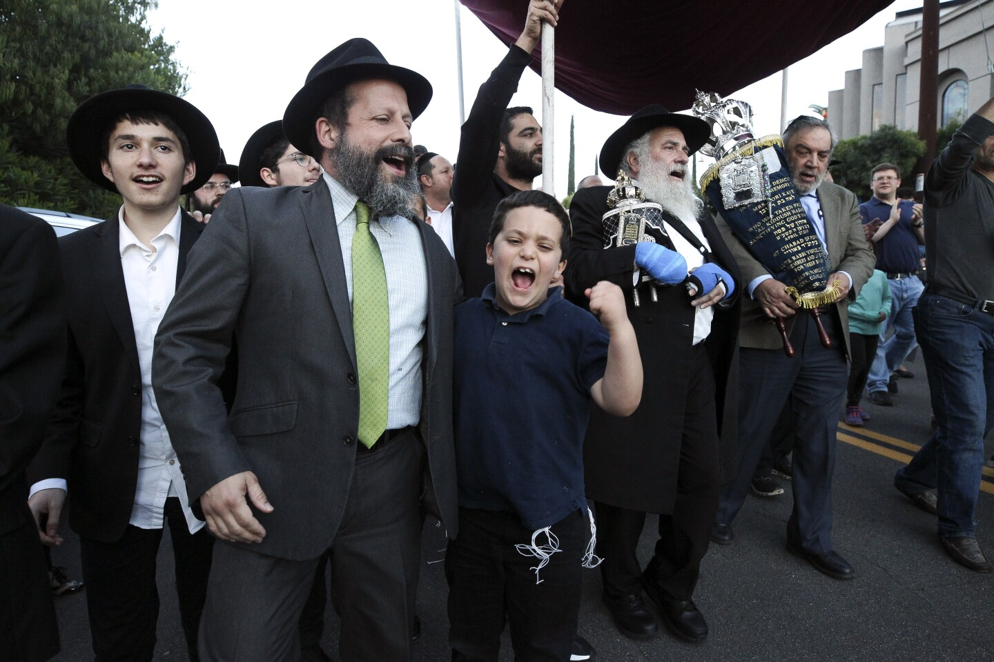 Synagogue members sing as the new torah is paraded outside of Chabad of Poway during a celebration for the completion of new torah that is dedicated to Lori Gilbert-Kaye, who was killed when a gunman attacked the synagogue last April, at Chabad of Poway on Wednesday, May 22, 2019 in Poway, California.