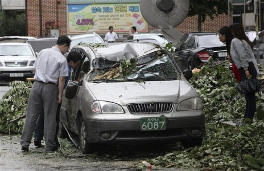 People look at a vehicle damaged by a fallen branch after Typhoon Kompasu hit in Seoul, South Korea, Thursday, Sept. 2, 2010. The typhoon slammed into South Korea on Thursday, killing three people in what officials said was the strongest tropical storm to hit the Seoul area in 15 years. The driver of the car is safe as the person was not in the car. (AP Photo/Ahn Young-joon)