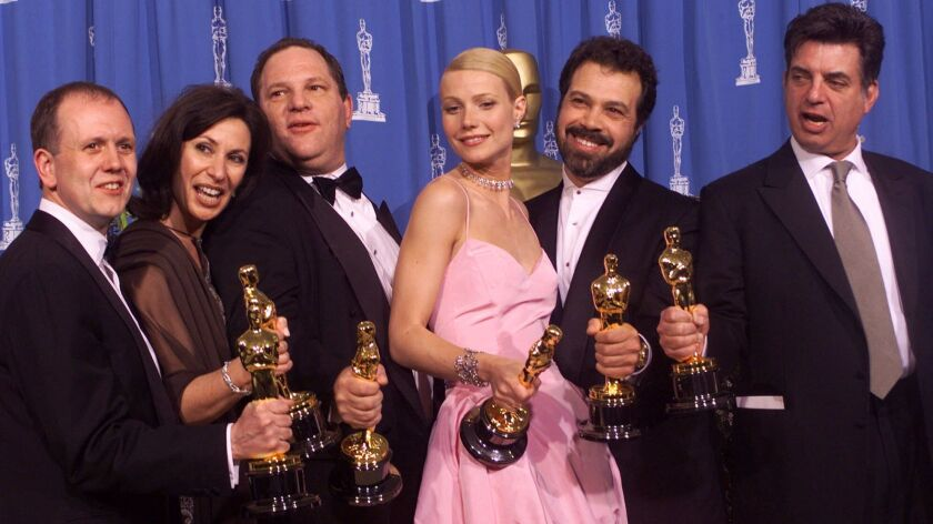 """In 1999, David Parfitt, from left, Donna Gigliotti, Harvey Weinstein, Gwyneth Paltrow, Edward Zwick and Marc Norman celebrate their Oscar wins for """"Shakespeare in Love."""""""