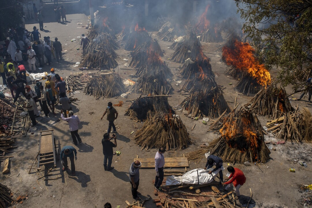 Flames and smoke rise from numerous funeral pyres