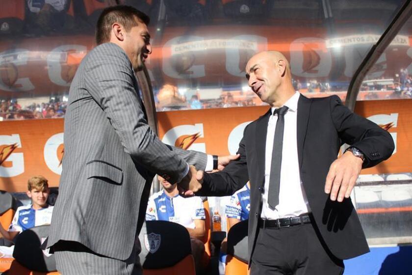 Los directores técnicos Pako Ayestaran de Pachuca (d) y Diego Alonso de Monterrey (i) se saludan, durante un partido. EFE/Archivo