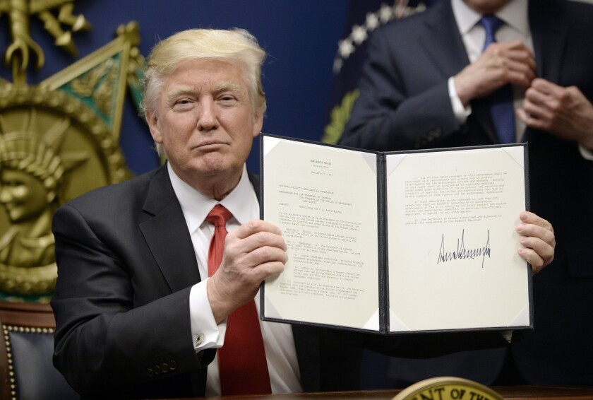 President Trump signs executive orders at the Department of Defense on Jan. 27. The one barring refugees and travel from seven majority-Muslim countries is making business more difficult, some entrepreneurs say.