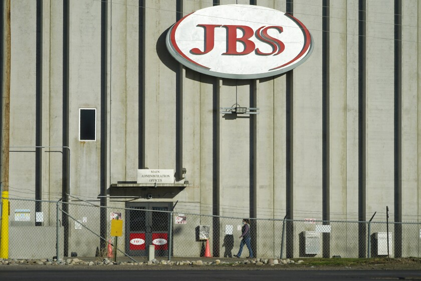 Worker heads into the JBS meatpacking plant in Greeley, Colo.