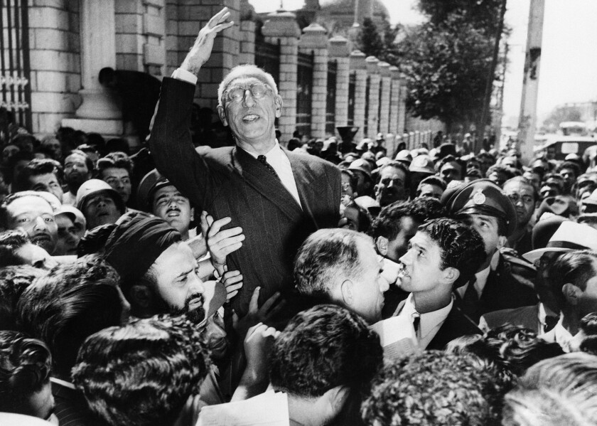 FILE - In this Sept. 27, 1951 file photo, Prime Minister Mohammad Mosaddegh rides on the shoulders of cheering crowds in Tehran's Majlis Square, outside the parliament building, after reiterating his oil nationalization views to his supporters. The U.S. ambassador to Iran mistakenly told the shah in 1953 that Britain's newly enthroned Queen Elizabeth II backed a plan to overthrow the country's elected prime minister and America maintained the fiction even after realizing the error, historians now say. (AP Photo, File)
