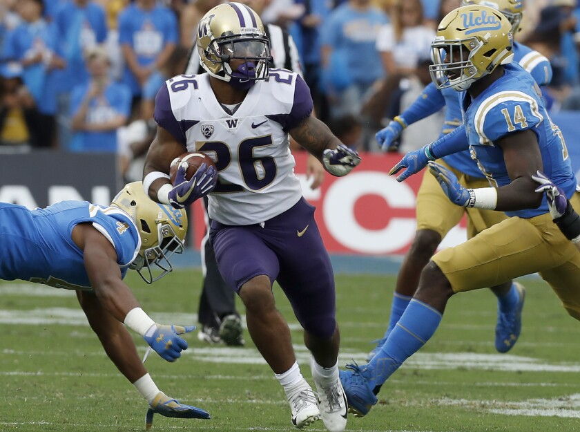 Washington running back Salvon Ahmed runs into the UCLA defensive backfield for a long gain in the first quarter on Saturday at the Rose Bowl.