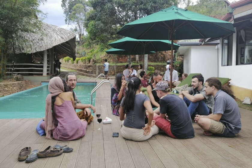 "In this April, 2020, photo, stranded tourists rest at the Cafe Chill in Ella, a tourist hot spot about 200 kilometers (120 miles) east of the capital Colombo, Sri Lanka. When flights were canceled and airports shut down, cafe owner Darshana Ratnayake decided to organize free food and shelter for several dozen stranded tourists. ""We were totally blown away,"" one of the tourists, 31-year-old cruise line entertainment director Alex Degmetich, said of the gesture. 40 tourists were stranded in Ella after the Sri Lankan government imposed a nationwide curfew on March 20 to curb the spread of the virus, sealing off entire regions of the Indian Ocean island nation. (Cafe Chill via AP)"