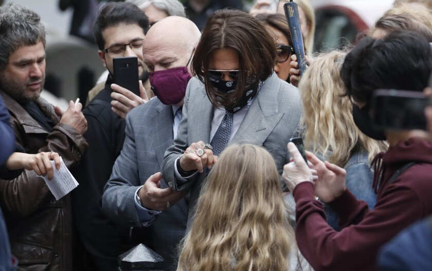 "Actor Johnny Depp, centre, is surrounded by fans as he arrives at the High Court in London, Thursday, July 16, 2020. Depp is suing News Group Newspapers, publisher of The Sun, and the paper's executive editor, Dan Wootton, over an April 2018 article that called him a ""wife-beater."" The Sun's defense relies on a total of 14 allegations by his ex-wife Amber Heard of Depp's violence. He strongly denies all of them. (AP Photo/Alastair Grant)"