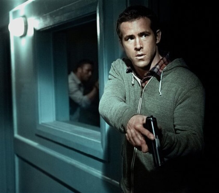 """In this film image released by Universal Pictures, Ryan Reynolds is shown in a scene from """"Safe House."""" (AP Photo/Universal Pictures, Jasin Boland)"""