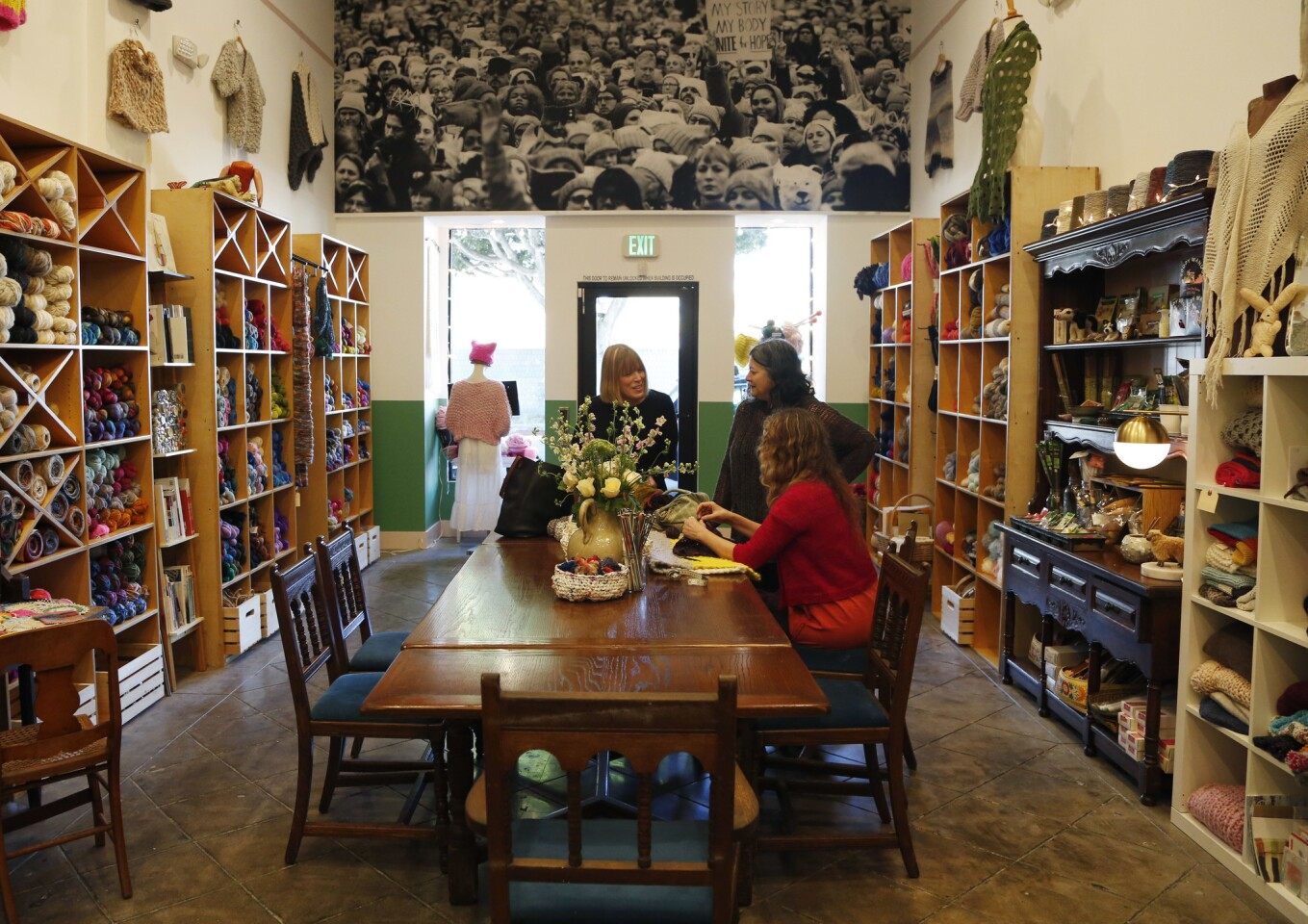 Little Knittery owner Kat Coyle, right, sitting, talks to customers at her yarn shop in Los Feliz.