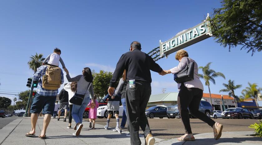 ENCINITAS, CA 11/24/2018: Pedestrians walk across South Coast Highway 101 at D Street, on Small Busi