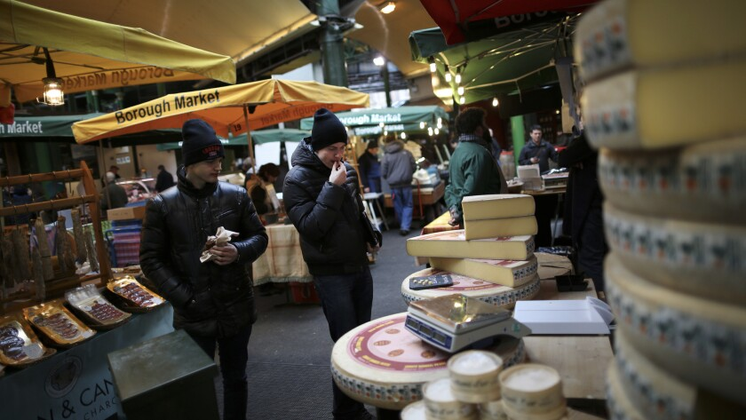 Customers try a free sample of cheese at Borough Market in London.
