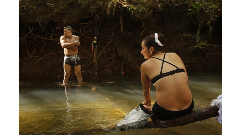 FARC member Viviana, age 28, right, and her comrade Jon, 34, bathe in the spring waters next to their camp.