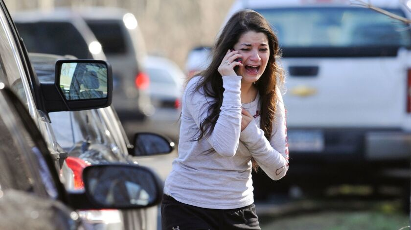 A woman waits to hear about her sister, a teacher, following a shooting at the Sandy Hook Elementary