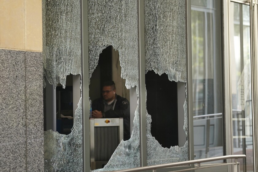 A man sits behind a broken window at a federal building in Oakland