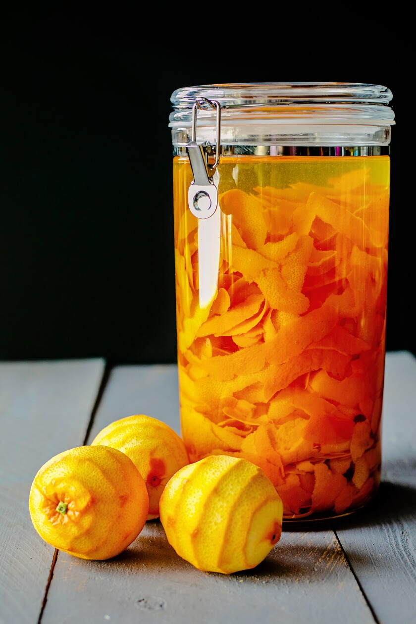 A container filled with orange peels and vodka.