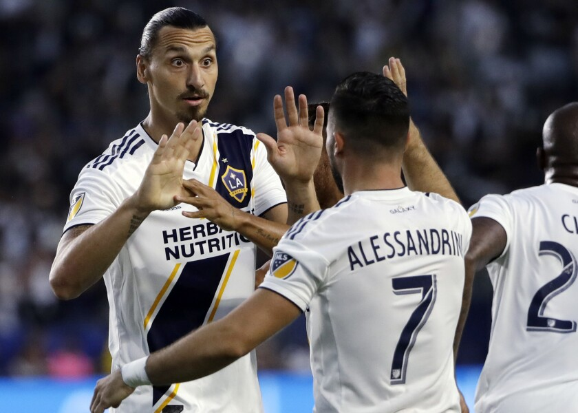 Galaxy forward Zlatan Ibrahimovic, being congratulated by midfielder Romain Alessandrini during a previous game, had a hat trick Sunday night.