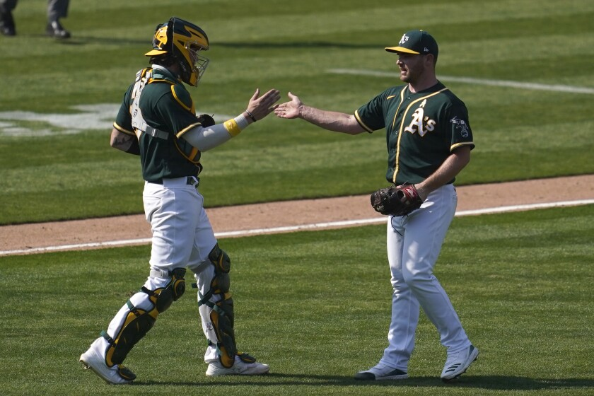 Oakland Athletics catcher Jonah Heim, left, celebrates with pitcher Liam Hendriks after the Athletics defeated the San Diego Padres in a baseball game in Oakland, Calif., Saturday, Sept. 5, 2020. (AP Photo/Jeff Chiu)