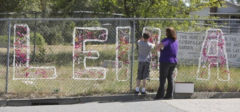 Teacher Cecilia Richardson helps a student tie a ribbon honoring murder victim, A student ties a ribbon to a fence honoring Leila Fowler at Jenny Lind Elementary School in Valley Springs, Calif., after the third-grader was stabbed to death at her home.