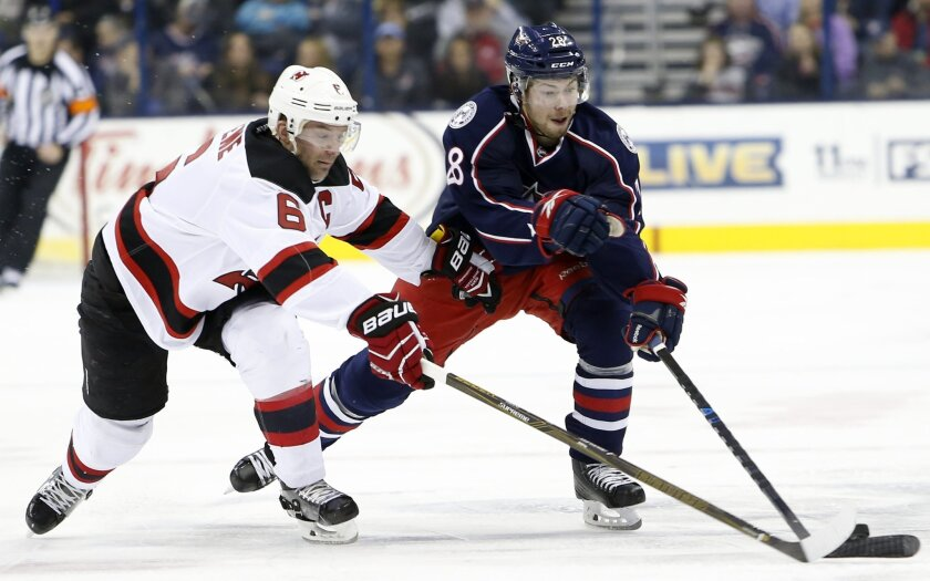 New Jersey Devil's Andy Greene, left, and Columbus Blue Jackets' Oliver Bjorkstrand, of Denmark, chase a loose puck during the first period of an NHL hockey game, Saturday, March 19, 2016, in Columbus, Ohio. (AP Photo/Jay LaPrete)