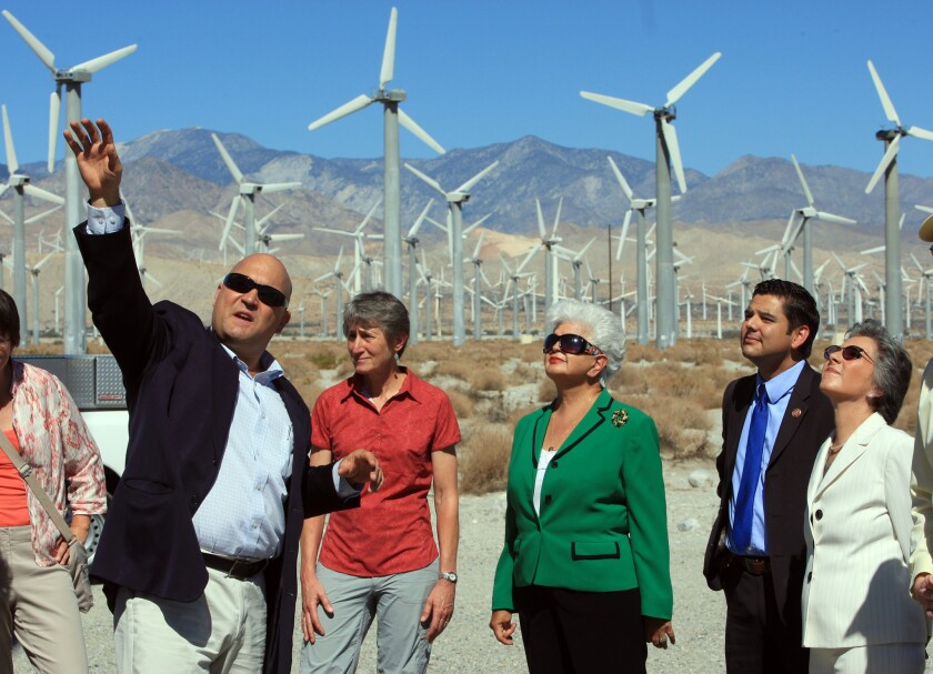 Rep. Grace Napolitano, center in green, tours a wind farm in Palm Springs. She is one of at least five California members of Congress who live outside the boundaries of their districts.