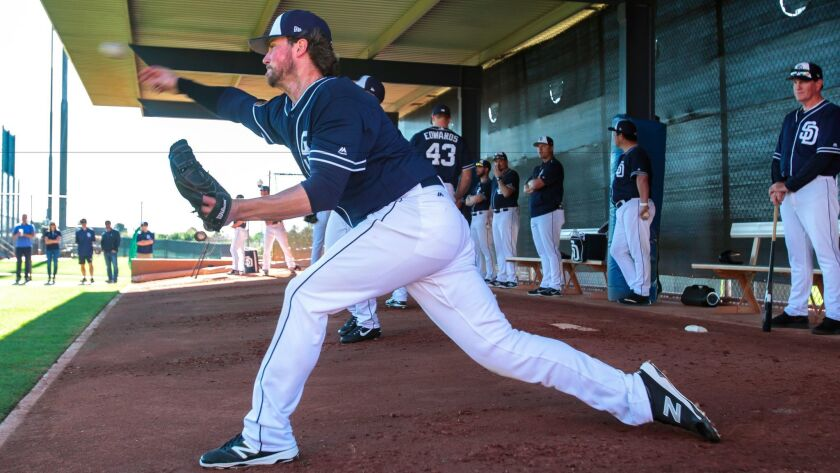 Padres pitcher Carter Capps throws in the bullpen as pitching coach Darren Balsley, far right, watches during spring training at the Peoria Sports Complex in Peoria, Ariz.
