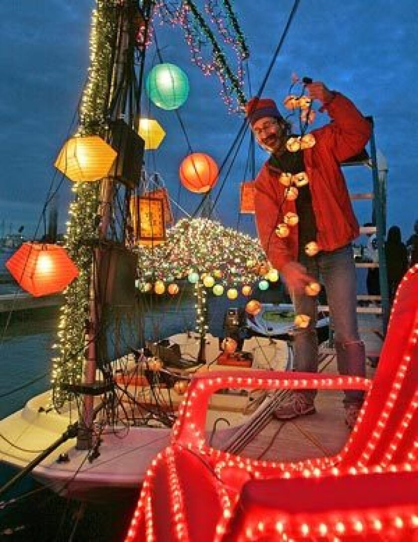 Skipper Peter Barbour strings lights on his boat in preparation for the Newport Beach Christmas boat parade.