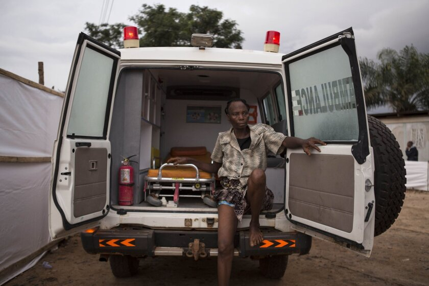 "In this photo taken on Wednesday, Sept. 24, 2014, a woman suspected of suffering from the Ebola virus sits in an ambulance in Kenema, Sierra Leone. Sierra Leone restricted travel Thursday, Sept. 25, 2014 in three more ""hotspots"" of Ebola where more than 1 million people live, meaning about a third"