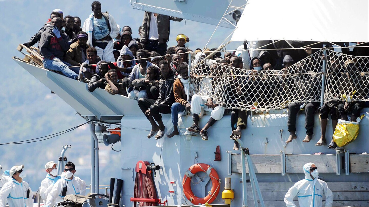 Migrants wait to disembark from the Italian navy vessel Chimera in the harbor of Salerno, Italy, Wednesday, April 22, 2015. Italy pressed the European Union on Wednesday to devise concrete, robust steps to stop the deadly tide of migrants on smugglers' boats in the Mediterranean, including setting up refugee camps in countries bordering Libya.