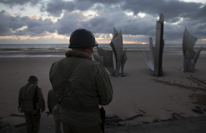 Two men in vintage US WWII uniforms walk toward the Les Braves monument at sunrise prior to a D-Day 76th anniversary ceremony in Saint Laurent sur Mer, Normandy, France, Saturday, June 6, 2020. Due to coronavirus measures many ceremonies and memorials have been cancelled in the region with the exception of very small gatherings. (AP Photo/Virginia Mayo)
