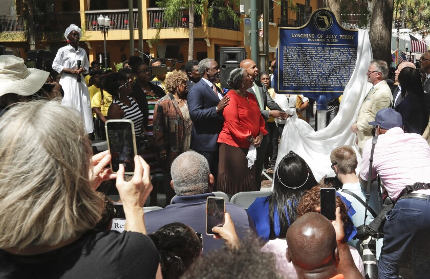 FILE- In this June 21, 2019 file photo, descendants of July Perry along with local elected officials and residents attend a ceremony unveiling a historical marker in Orlando, Fla. Perry was lynched by a white mob after helping a friend trying to vote. After Perry was lynched, the mob laid siege to the black section of Ocoee, Fla., killing dozens. (AP Photo/John Raoux, File)