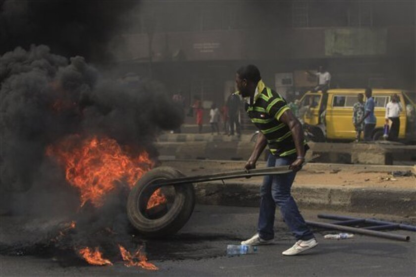 A Protester set fire on a major road in commercial capital during a fuel subsidy protest in Lagos, Nigeria, Tuesday, Jan. 3, 2012. Angry mobs of protesters stopped gas station owners from selling fuel Tuesday while others lit a bonfire on a major highway in an attempt to thwart the government's removal of a cherished consumer subsidy that had kept gas affordable for more than two decades. (AP Photo/Sunday Alamba)