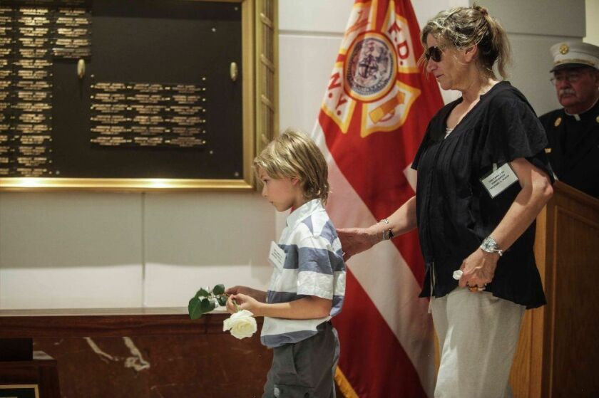 Corrina Duffy, with nephew Frankie Loccisano, 8, place a flower to honor her husband Firefighter Michael Duffy during the Memorial Wall Dedication Ceremony, honoring WTC illness-related deaths at 9 Metro Tech Center in Brooklyn on Thursday