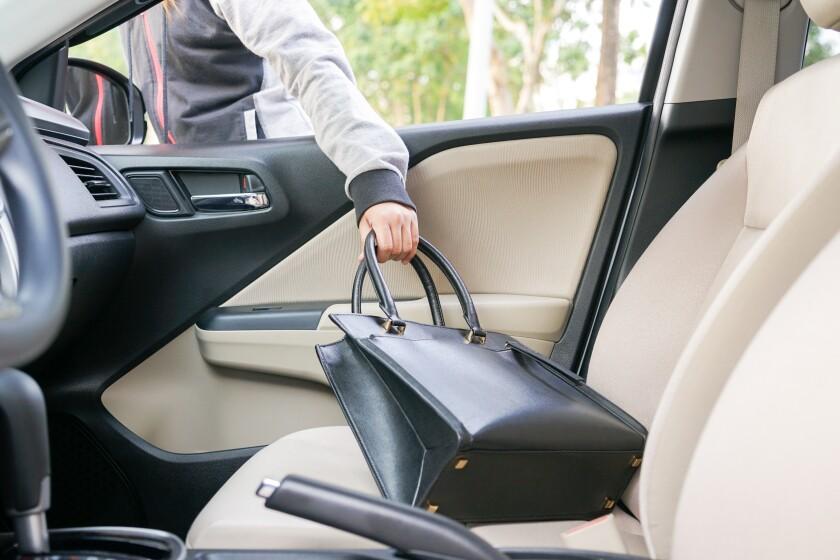 Woman burglar steal a shoulder bag through the window of car - theft concept