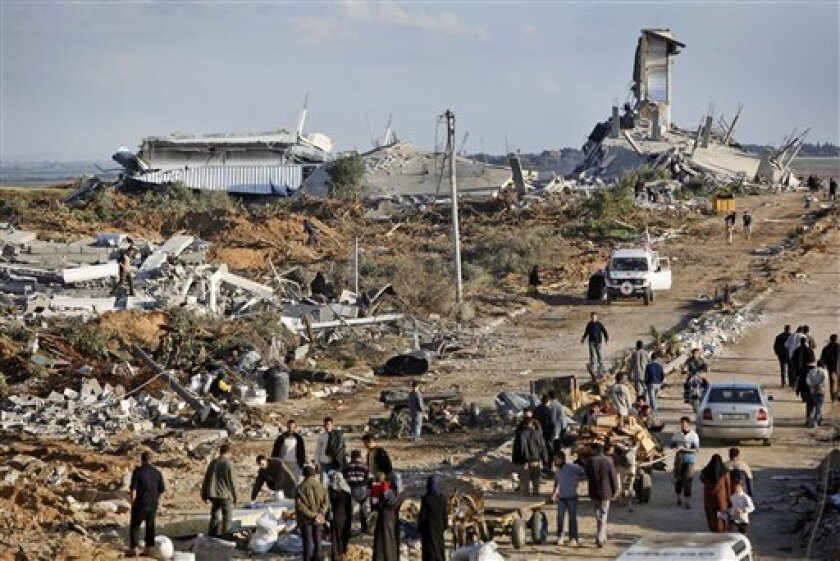 Residents return to the heavily hit eastern area of Jebaliya, in the northern Gaza strip, Sunday, Jan. 18, 2009. Hamas offered Israel an immediate weeklong truce Sunday, hours after Israel silenced its guns and grounded its aircraft, but the Islamic militant group conditioned long-term quiet on a c