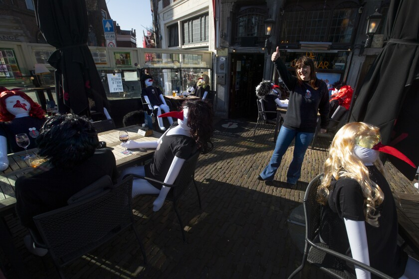 Cafe De Ooievaar owner Mary Schepers flashes a thumbs up to passing customers on her terrace filled with inflatable dolls in Delfshaven, Rotterdam, Netherlands, Tuesday, March 2, 2021. Stores in one village opened briefly, cafe owners across the Netherlands were putting tables and chairs on their outdoor terraces and sex workers were planning a demonstration outside parliament in protests against the government's tough coronavirus lockdown. (AP Photo/Peter Dejong)