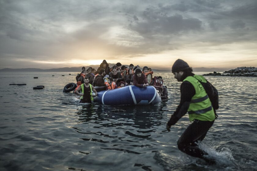 """In this Feb. 16, 2016 photo provided by Oxfam, a boat filled with refugees reaches the shore of the small Greek island of Lesbos. The photo will be among those included in """"The Refugee Road,"""" an interactive exhibit presented by Oxfam America and Microsoft on Wednesday evening, May 25, 2016, at Microsoft's office in Cambridge, Mass. Oxfam is using the free event to call on the U.S. to redouble its efforts to resettle Syrians. (Pablo Tosco/Oxfam via AP)"""