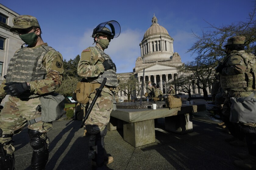 Members of the Washington National Guard stand at a sundial near the Legislative Building, Sunday, Jan. 10, 2021, at the Capitol in Olympia, Wash. Governors in some states have called out the National Guard, declared states of emergency and closed their capitols over concerns about potentially violent protests. Though details remain murky, demonstrations are expected at state capitols beginning Sunday and leading up to President-elect Joe Biden's inauguration on Wednesday. (AP Photo/Ted S. Warren)