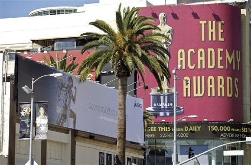 """A commercial billboard described as a """"supergraphic"""" ad for Asics sports wear, left, is seen on Hollywood Boulevard in Los Angeles on Thursday, March. 4, 2010. The Los Angeles city attorney's office has filed its first charges under a ban passed last year on the giant building-cloaking signs known as super graphics and most other digital billboards. The civil complaint filed Monday accuses 27 billboard companies, property owners and sign installers of violation of the ban approved in August by the City Council. (AP Photo/Damian Dovarganes)"""