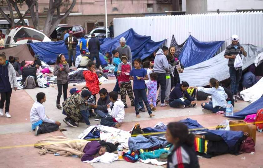 Migrantes esperan afuera de un cruce fronterizo en Tijuana, México.