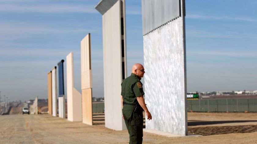 Mario Villarreal, the field office division chief for Customs and Border Protection, walks near the border wall prototypes that were built east of San Ysidro on the border of Mexico, shown here on Monday, Nov. 20, 2017.