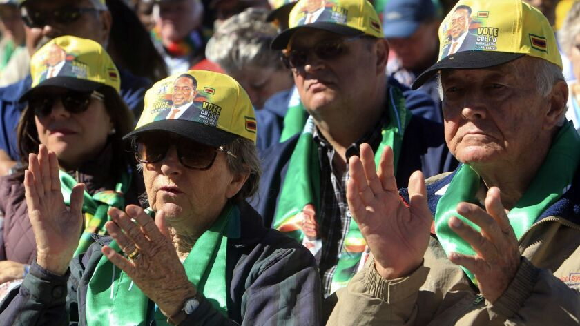 Supporters of Zimbabwean President Emmerson Mnangagwa listen to his address during a rally organized