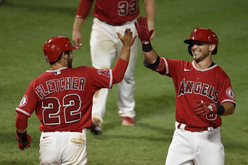 The Angels' Tommy La Stella celebrates with David Fletcher after hitting a walk-off, two-run home run Aug. 17, 2020.
