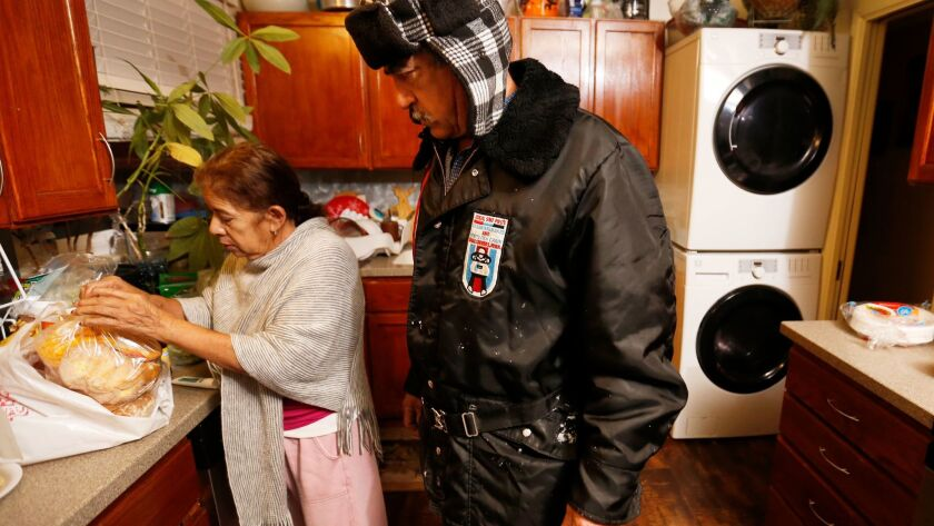 Jorge Alcala's wife, Belen, helps him get ready in the morning before work.