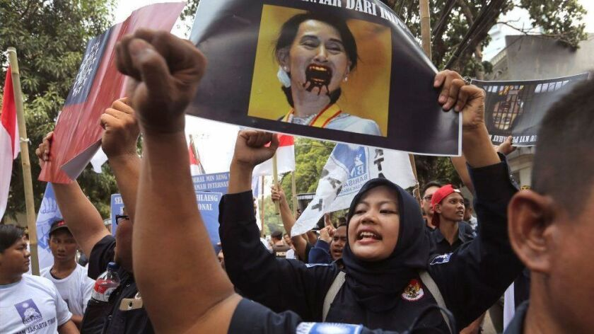 A Muslim woman shouts slogans while holding a defaced portrait of Myanmar's leader Aung San Suu Kyi during a rally outside Myanmar's Embassy in Jakarta, Indonesia.