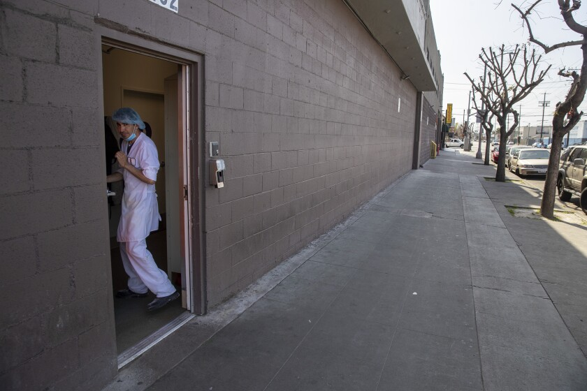 An employee at Rockenwagner Bakery heads back into the building after ordering food from a taco truck parked on West Adams Blvd. on Saturday, April 4, 2020 in West Adams, CA. (