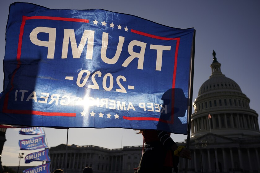 A supporter of President Donald Trump holds a Trump 2020 flag outside the U.S. Capitol building as they attend pro-Trump marches, Saturday Nov. 14, 2020, in Washington. (AP Photo/Jacquelyn Martin)