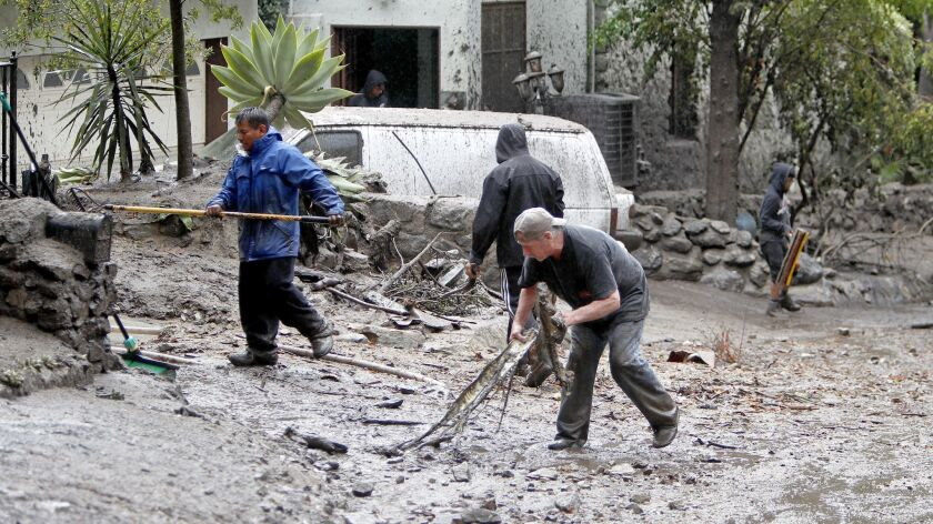 Local residents remove debris and mud from in front of their home on Country Club Drive in Burbank o
